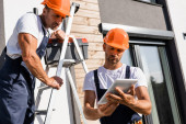 Workmen with ladder and toolbox using digital tablet near building