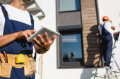 Selective focus of manual worker using digital tablet while colleague standing on ladder near facade of house