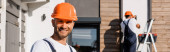Panoramic shot of builder looking at camera while colleague working near building at background