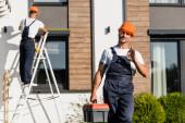 Selektiver Fokus des Bauarbeiters in Uniform mit Werkzeugkiste, die ok Geste zeigt, während der Kollege in der Nähe des Gebäudes arbeitet