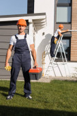 Selective focus of builder with gloves an toolbox standing on lawn while colleague working on ladder near house