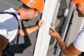 Szelektív fókusz az építők nézi a spirituális szint, miközben dolgozik homlokzata ház