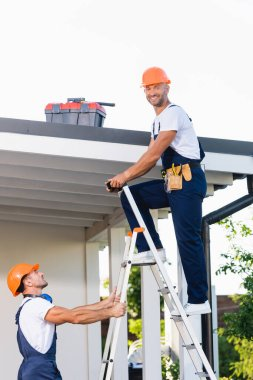 Side view of builder looking at camera while standing on ladder near colleague and building stock vector