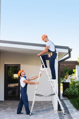 Side view of builder standing near colleague on ladder and building on urban street stock vector