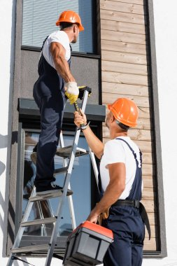 Selective focus of workman with toolbox giving hammer to colleague on ladder near building stock vector