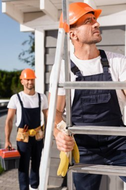 Selective focus of builder in hardhat standing on ladder near colleague and building stock vector