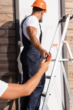 Selective focus of builder giving pliers to colleague on ladder near house stock vector