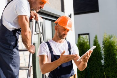 Selective focus of builder on ladder standing near colleague pointing with hand on digital tablet near building stock vector