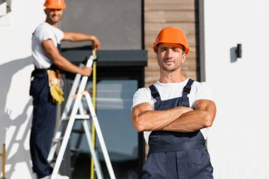 Selective focus of builder with crossed arms looking at camera with colleague and building at background stock vector