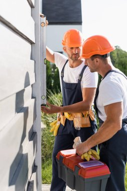 Selective focus of workmen with tools using spirit level while working with facade of building stock vector