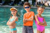 Junge mit Sonnenbrille und Mädchen in Badeanzügen posieren mit verschränkten Armen am Pool