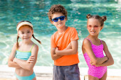 girls in swimsuits and curly boy in sunglasses standing with crossed arms near pool