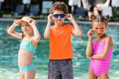Lockenkopf im T-Shirt und Mädchen in Badeanzügen berühren Sonnenbrille am Pool