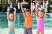 Mädchen in Badeanzügen und Junge im T-Shirt stehen mit den Händen in der Luft am Pool