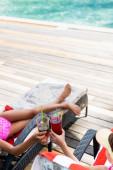 vysoký úhel pohledu dívek sedících na lehátkách a cinkajících sklenicích s čerstvými koktejly