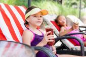 selektiver Fokus des Mädchens mit Schirmmütze, das in der Sonnenbank neben einem Freund sitzt und ein Glas frischen Cocktails in der Hand hält