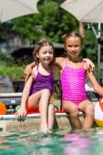 Kinder in Badeanzügen sitzen mit Beinen im Wasser am Pool, umarmen sich und schauen in die Kamera