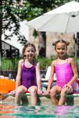 Freunde in Badeanzügen sitzen mit Beinen im Wasser am Pool und schauen in die Kamera