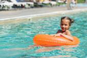 gyermek úszó medencében úszás gyűrű és nézi a kamera