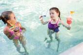 Fotografie Mädchen blickt in Kamera, während sie Sonnenbrille und Fruchtcocktail in Pool nahe Freund hält