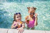 Fotografie Mädchen berührt Sonnenbrille, während sie im Pool neben Freund mit erfrischendem Cocktail steht