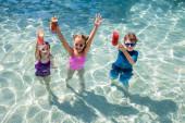 Blick von oben auf Kinder, die im Pool stehen und frische Fruchtcocktails in erhobenen Händen halten