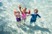 Hochwinkelblick aufgeregter Freunde mit Gläsern mit frischen Cocktails im Swimmingpool