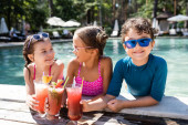 Fotografie Fröhliche Kinder in Badebekleidung klappern in Poolnähe an frischen Fruchtcocktails