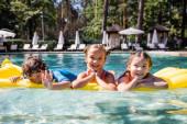 Fotografie fröhlicher Junge winkt mit der Hand in die Kamera, während er mit Mädchen auf aufblasbarer Matratze schwimmt
