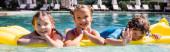 panoramatický koncept chlapce mávání rukou na kameru při plavání na nafukovací matraci s dívkami