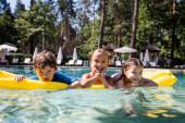 Fotografie selektiver Fokus von Mädchen und Jungen, die auf aufblasbaren Matratzen im Schwimmbad schwimmen