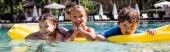 horizontální obraz radostných přátel při pohledu na kameru při plavání na nafukovací matraci v bazénu
