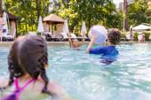 Selektiver Fokus von Freunden, die im Schwimmbad mit aufblasbarem Ball spielen