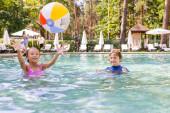 Selektiver Fokus aufgeregter Freunde beim Spielen mit aufblasbarem Ball im Schwimmbad
