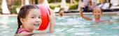 selektiver Fokus des Mädchens mit aufblasbarem Ball in der Nähe eines Freundes, der im Schwimmbad winkt, panoramisches Konzept