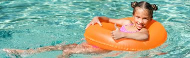 Horizontal crop of joyful girl showing thumb up while floating in pool on inflatable ring stock vector