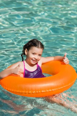 Joyful kid showing thumbs up while swimming in pool on inflatable ring stock vector
