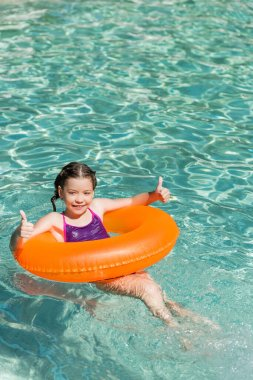 Joyful child showing thumbs up while floating in pool on swim ring stock vector
