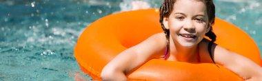 Horizontal image of joyful girl swimming on inflatable ring in pool near water splashes stock vector