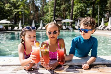 Friends in swimwear clinking glasses with fresh fruit cocktails near pool stock vector