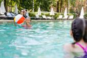 Mädchen hält aufblasbaren Ball neben Freundin im Schwimmbad