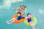 vysoký úhel pohledu radostných přátel mávající rukama a při pohledu na fotoaparát při plavání v bazénu na plaveckých kroužcích