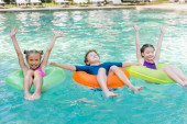 Fotografie joyful girls with hands in air and boy with closed eyes floating in pool on swim rings