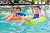 radostní přátelé při pohledu na fotoaparát při plavání v bazénu na pestrobarevných plaveckých kroužcích
