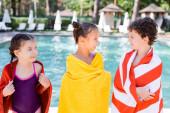 Mädchen im Badeanzug in der Nähe von Freunden, die sich beim Einwickeln in Frottee-Handtücher anschauen