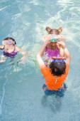 Hochwinkel-Ansicht von Freunden, die High Five geben, während sie Spaß im Schwimmbad haben