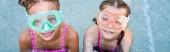 Fotografie Blick von oben auf zwei Mädchen in Schwimmmasken, die in Poolnähe in die Kamera schauen, horizontaler Schnitt
