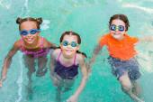 Hochwinkelaufnahme von Mädchen und Jungen mit Schwimmbrille, die in die Kamera schauen, während sie Spaß im Pool haben