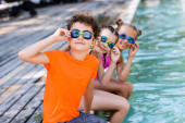 selective focus of friends touching swim goggles while sitting near pool and looking at camera