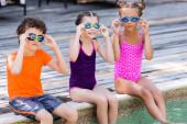 Mädchen in Badeanzügen und Junge im T-Shirt berühren Schwimmbrillen, während sie auf dem Pooldeck sitzen